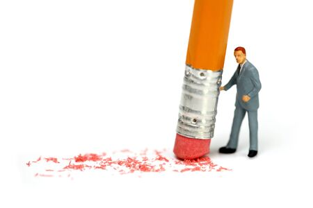 Miniature businessman holds a pencil and erases a mistake. Business mistake concept.