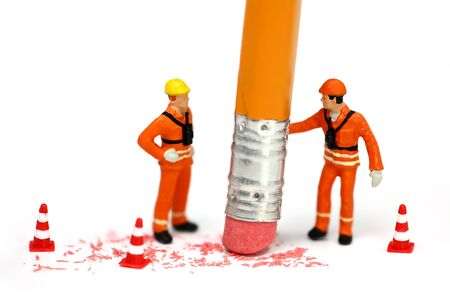 Miniature engineer or technician holds a pencil and erases a mistake while his associate watches. Engineering mistake concept.