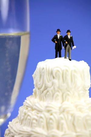 Miniature couple standing on top of a wedding cake. There is a glass of champagne in the background