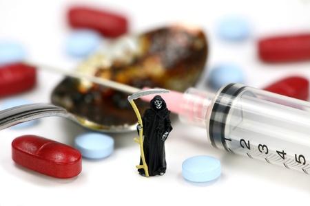 drogadiccion: Concepto de adicci�n a las drogas. Una guada�a en miniatura se encuentra en frente de una jeringa, pastillas y una cuchara con recubrimiento de hero�na. Fondo blanco. Foto de archivo