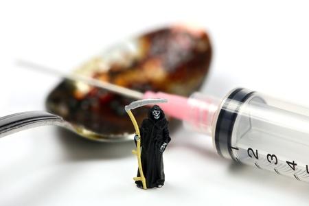drogadiccion: Concepto de adicci�n a las drogas. Una guada�a en miniatura se encuentra en frente de una cuchara con recubrimiento de jeringa y hero�na. Fondo blanco.