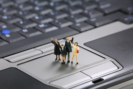 Miniature family waves for help with their laptop computer. Tech support concept. photo
