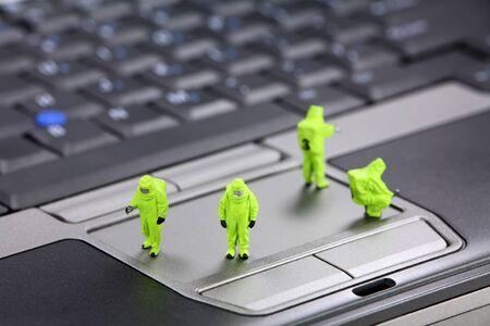 viruses: Equipo del HAZMAt (materiales peligrosos) de miniatura inspecciona un equipo port�til para virus, spyware y troyanos. Concepto de seguridad del equipo. Foto de archivo