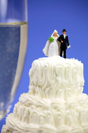 Miniature bride and groom on top of a wedding cake. There is a glass of champagne in the background. Marriage concept. photo