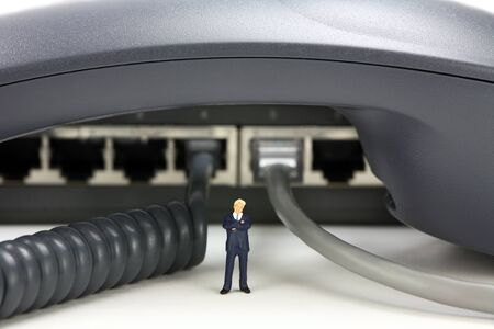 IP Telephony concept. Miniature businessman stands underneath a phone with a switch in the background. A phone cord and network cable are plugged into the switch.