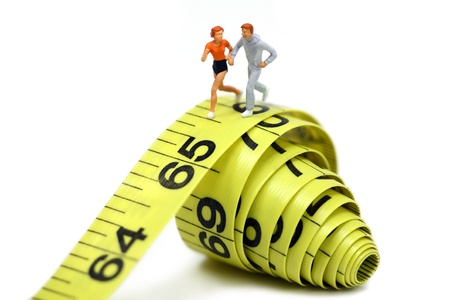 Miniature joggers run on a rolled up yellow measuring tape. Active and healthy lifestyle concept. photo