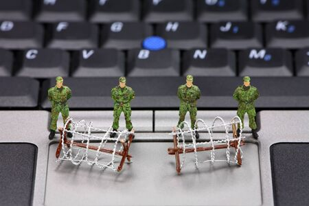 miniature people: Miniature military soldiers and barbed wire are guarding a laptop from viruses, spyware and identity thieves. Computer security concept. Stock Photo