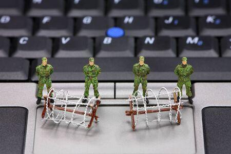 virus informatico: Soldados militares en miniatura y alambre de p�as est�n protegiendo un port�til de virus, software esp�a y ladrones de identidad. Concepto de seguridad del equipo.
