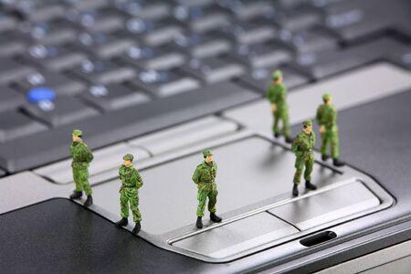 virus informatico: Soldados militares en miniatura est�n protegiendo un port�til de virus, software esp�a y y ladrones. Concepto de seguridad del equipo.