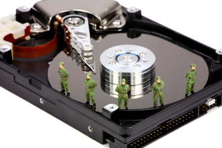 Miniature military soldiers are guarding a computer hard drive from viruses, spyware and identity thieves. Computer data security concept. Stock Photo - 8954514