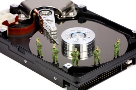 identity thieves: Soldados militares en miniatura est�n protegiendo un disco duro del equipo frente a virus, software esp�a y ladrones de identidad. Concepto de seguridad de datos de equipo. Foto de archivo