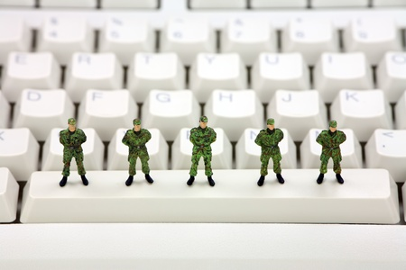 Miniature military soldiers are standing on a computer keyboard guarding it from viruses, spyware and identity thieves. Computer security concept. photo