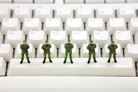 identity thieves: Soldados militares en miniatura est�n de pie en un teclado de computadora lo protecci�n frente a virus, software esp�a y ladrones de identidad. Concepto de seguridad del equipo.