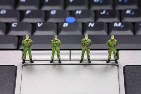 viruses: Soldados militares en miniatura est�n protegiendo un port�til de virus, software esp�a y ladrones de identidad. Concepto de seguridad del equipo.