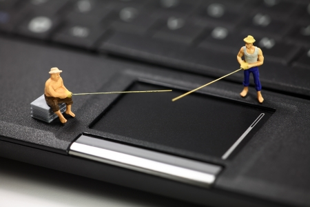 email: Miniature fisherman representing online email phishing scams. Online phishing and identity theft concept.