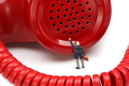Miniature businessman stands in front of a red telephone receiver waving for help. He feels small and helpless. IT support or customer service concept. Stock Photo - 8949362