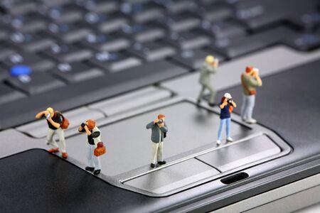 Miniature photographers stand on a laptop computer. Paparazzi concept.
