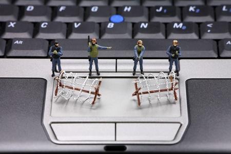 identity thieves: Equipo de swat en miniatura y alambre de p�as est�n protegiendo un port�til de virus, software esp�a y ladrones de identidad. Concepto de seguridad del equipo. Foto de archivo