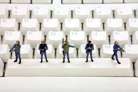 viruses: Equipo de swat en miniatura es permanente en un teclado de computadora lo protecci�n frente a virus, software esp�a y ladrones de identidad. Concepto de seguridad del equipo.