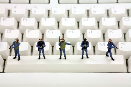 figurines: Miniature swat team is standing on a computer keyboard guarding it from viruses, spyware and identity thieves. Computer security concept. Stock Photo