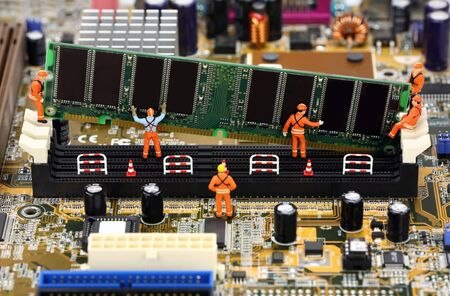 motherboard: Miniature construction workers installing RAM memory on a computer motherboard. Stock Photo
