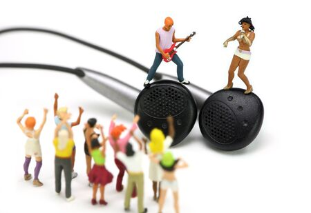 Miniature singer and guitar player standing on a pair of ear buds. There are miniature fans cheering for them in the foreground. White background. photo