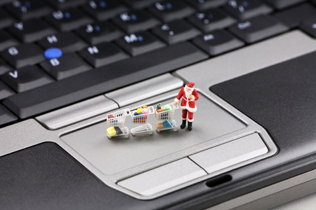 Online Christmas shopping concept. Miniature Santa Claus standing on a laptop pushing several shopping carts. Stock Photo