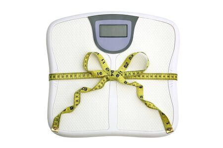 A scale with a tape measure wrapped around it tied in a bow. The display window is blank for your text.  White background. Dieting concept. Stock Photo