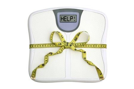 weighing scales: Una scala con una misura di nastro avvolto intorno ad esso legati in un inchino. Nella finestra dice aiuto!  Sfondo bianco. Concetto di dieta.