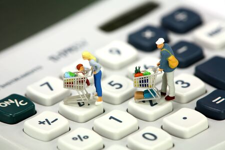 Shopping concept. Miniature shoppers with shopping carts standing on a calculator. Stock Photo