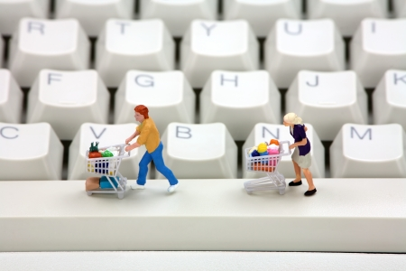 Miniature shoppers with shopping carts on a computer keyboard. Online shopping concept. Stock Photo