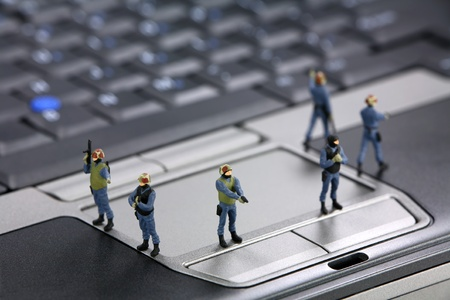 figurines: Miniature swat team are guarding a laptop from viruses, spyware and identiy thieves. Computer security concept. Stock Photo