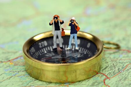 figurine: Travel concept. Miniature tourists taking pictures while standing on a compass. There is a map under the compass.