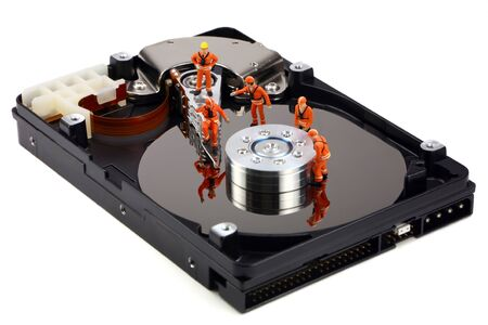 Miniature technicians closely inspecting a hard drive for viruses, spyware and trojans. Computer technican concept. Stock Photo - 8949354