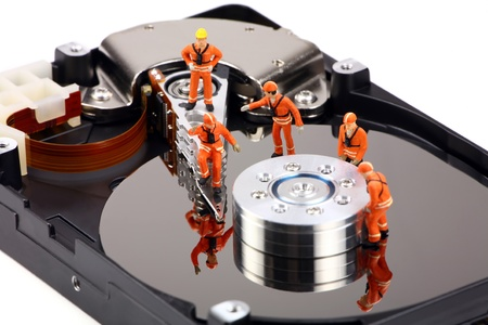 Miniature technicians closely inspecting a hard drive for viruses, spyware and trojans. Computer technican concept.