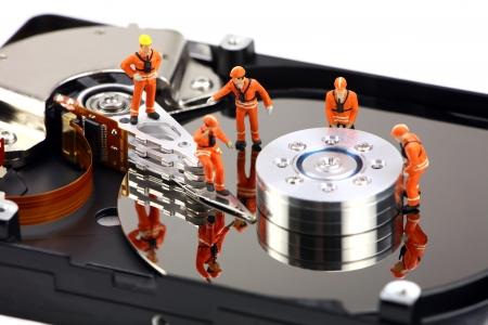 disco duro: T�cnicos de miniatura estrechamente inspeccionar una unidad de disco duro de virus, spyware y troyanos. Concepto de equipo t�cnico.