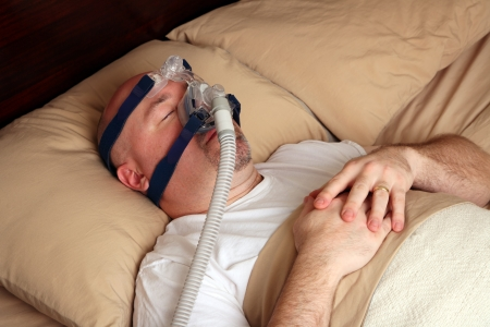 apnoe: Caucasian Mann mit Schlaf-Apnoe mit einem CPAP-Maschine im Bett. Lizenzfreie Bilder