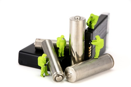 Concept image of a miniature HAZMAT team disposing of or recycling old batteries. Isolated on white background.