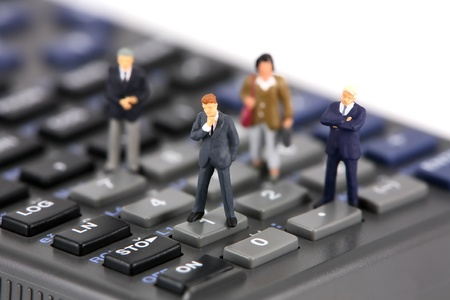 Concept image of a group of miniature businessmen and businesswomen standing on the keys of a scientific calculator. Focus is on the man in the center.