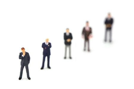 A group of miniature businessmen standing in a row diagonally. Focus in on the man in the bottom left corner. The rest of out of focus due to shallow depth of field. Leadership concept.