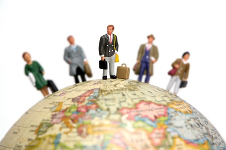 transnational: A group of miniature bussinessmen and businesswomen standing on a globe. Focus is on the man in the center with the others out of focus.