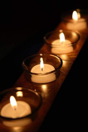 candle wick: A row of small candles in glass candle holders arranged diagonally. Stock Photo