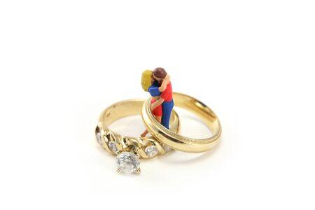 verlobt: Ein Miniatur-Paar ist umarmen und küssen innerhalb zwei Trauringe. Sie sind vor einem weißen Hintergrund. Könnte für eine Heirat oder Liebe Konzept verwendet werden. Lizenzfreie Bilder
