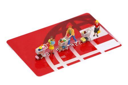 concept images: Concept immagini degli acquirenti con carrelli sulla cima di una carta di credito non di marca. Isolato su sfondo bianco.
