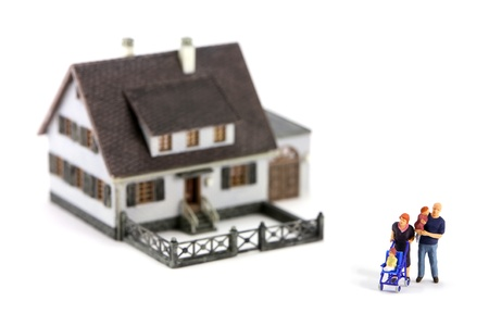 A miniature model home with a family in front. The focus is on the family and the home is out of focus due to shallow depth of field. Isolated on white background. Stock Photo - 9027111