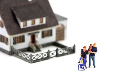 A miniature model home with a family in front. The focus is on the family and the home is out of focus due to shallow depth of field. Isolated on white background. photo