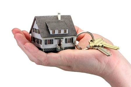 Concept image of a hand holding house keys. The miniature model house acts as a key ring with house keys hanging from it. White background. Stock Photo