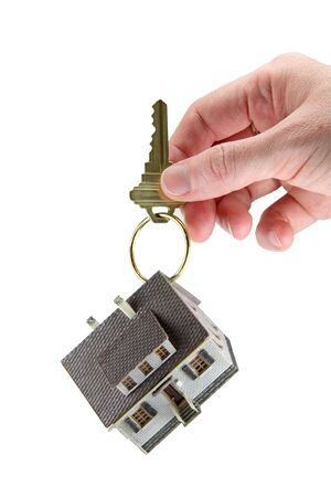Concept image of a hand holding a house key with a miniature model house hanging from the key ring. White background. photo