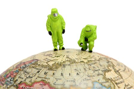 represents: Concept image of two miniature HAZMAT (Hazerdous Materials) figures standing on top of a globe. This can represents global warming, nuclear disaster or environmental issues. Stock Photo