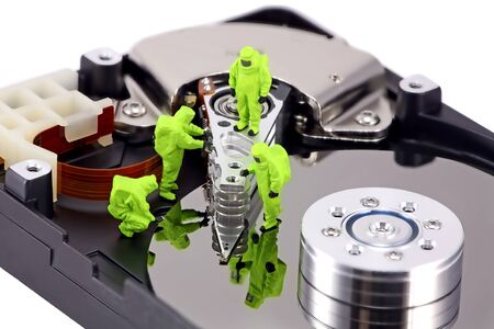 hazmat: Concept image of a HAZMAT (Hazardous Materials) team closely inspecting a hard drive for viruses, spyware and trojans.